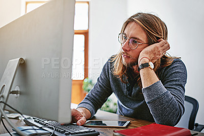 Buy stock photo Shot of a bored looking young man working on a computer at his desk in an office
