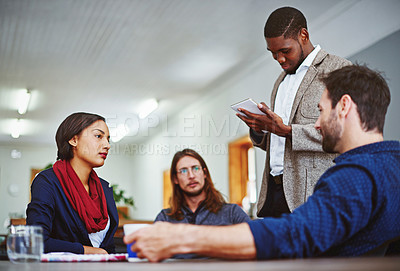 Buy stock photo Shot of a young man leading a meeting with coworkers in an office
