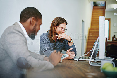 Buy stock photo Shot of two colleagues working together with a digital tablet and computer at a desk in an office