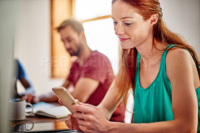 Buy stock photo Shot of a young woman sitting at a desk in an office using a digital tablet with colleagues in the background