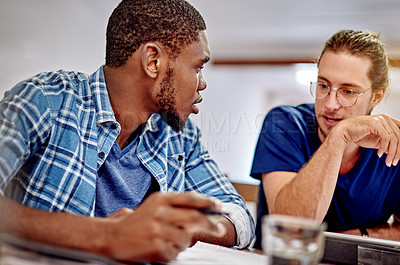 Buy stock photo Shot of two young colleagues talking together while working at a desk in an office