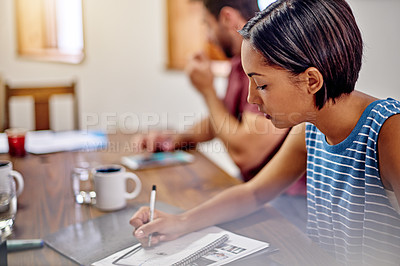 Buy stock photo Shot of a young woman writing in notebook while sitting at a table in an office