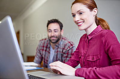 Buy stock photo Shot of colleagues working together on a laptop in an office