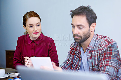 Buy stock photo Shot of two colleagues talking together over a digital tablet while working in an office