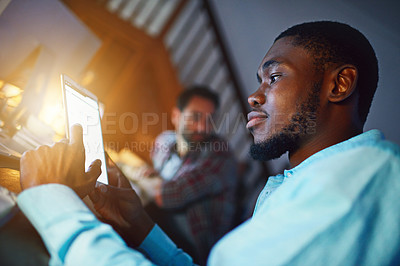 Buy stock photo Shot of a man working on a digital tablet in an office in the evening with colleagues in the background