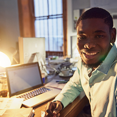 Buy stock photo Portrait of a smiling young man working on a laptop in an office in the evening