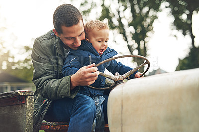 Buy stock photo Cropped shot of a father and his little son playing together on a farm tractor outside
