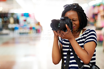 Buy stock photo Shot of a young female tourist snapping photographs inside a grocery store