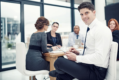 Buy stock photo Portrait of a businessman using a digital tablet during a meeting with his colleagues
