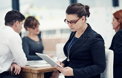 Buy stock photo Cropped shot of a businesswoman using a digital tablet during a meeting with her colleagues