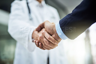 Buy stock photo Cropped shot of a doctor shaking hands with a businessman