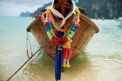 Buy stock photo Shot of a boat on the water with a colorful floral garland hanging from it