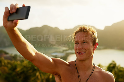 Buy stock photo Shot of a happy young man taking a selfie with his cellphone while on holiday