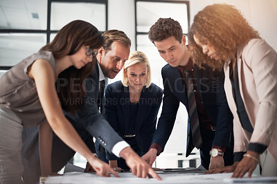 Buy stock photo Cropped shot of a team of professionals working on blueprints in an office