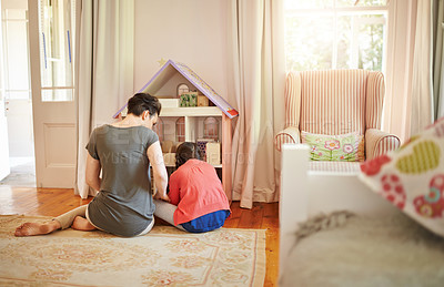 Buy stock photo Rearview shot of a young mother and her daughter playing with a dollhouse