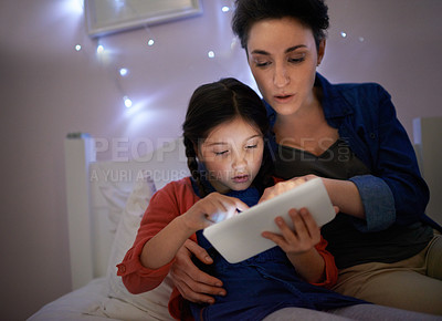 Buy stock photo Shot of a young mother and her daughter looking at a tablet while sitting on the bed