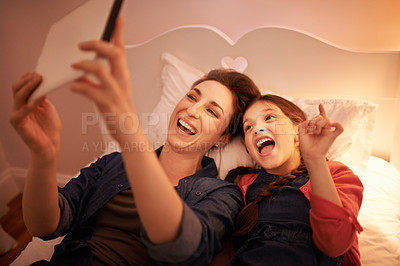 Buy stock photo Shot of a young mother and her daughter taking selfies on a bed at home