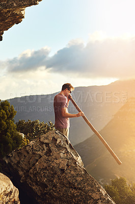 Buy stock photo Shot of a young man standing on a mountain top