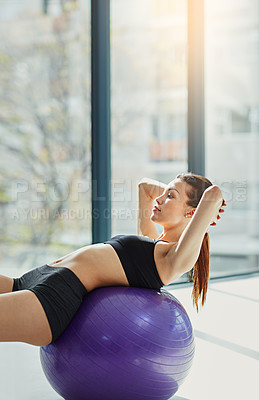 Buy stock photo Shot of an attractive young woman doing situps on an exercise ball at home