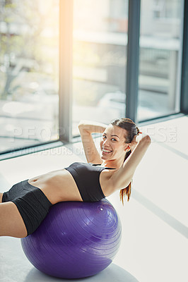 Buy stock photo Portrait of an attractive young woman doing situps on an exercise ball at home