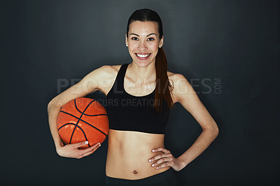 Buy stock photo Studio shot of a young woman holding a basketball against a dark background