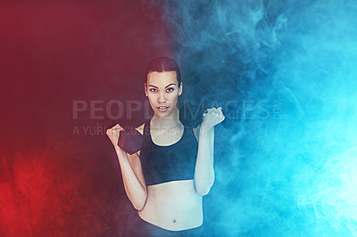 Buy stock photo Shot of a young woman working out with dumbbells