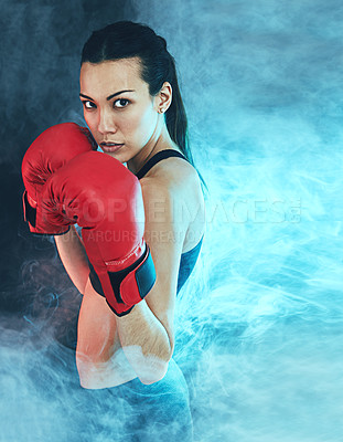 Buy stock photo Shot of a young woman wearing boxing gloves against a dark background