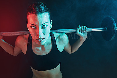 Buy stock photo Shot of a young woman lifting weights against a dark background