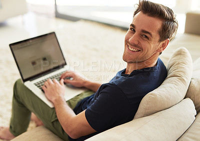 Buy stock photo High angle portrait of a handsome young man using his laptop at home