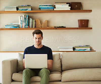 Buy stock photo Shot of a handsome young man using his laptop while sitting on the sofa at home