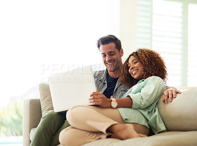 Buy stock photo Cropped shot of an affectionate young couple using a laptop in their home