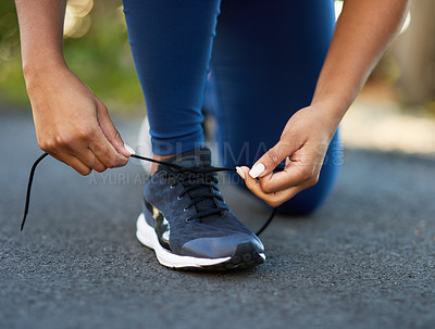 Buy stock photo Cropped shot of an unrecognizable young woman tying her laces before a workout