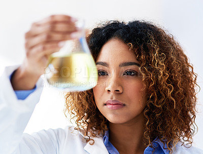 Buy stock photo Cropped shot of a young female scientist conducting an experiment in the lab