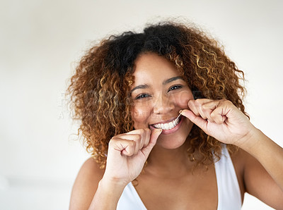 Buy stock photo Shot of a young woman flossing her teeth