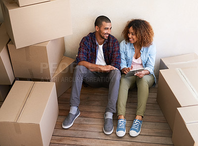 Buy stock photo Shot of a young couple using a tablet while sitting among boxes on moving day