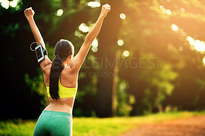 Buy stock photo Rearview shot of a sporty young woman celebrating a victory