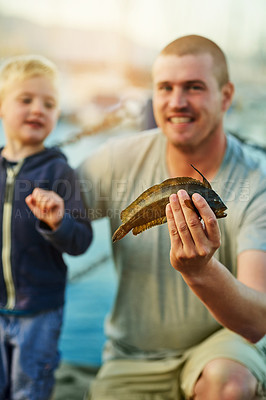 Buy stock photo Portrait of a father and his little boy fishing together at the harbor
