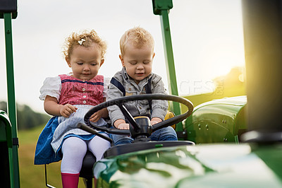 Buy stock photo Shot of two adorable children riding a tractor together on a farm