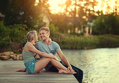 Buy stock photo Shot of an affectionate young couple sitting together at a lake outside