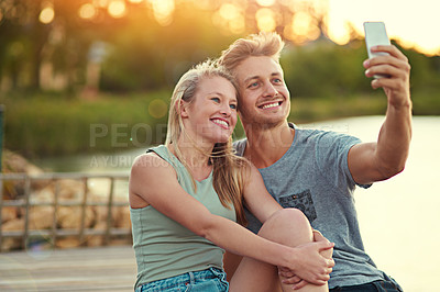 Buy stock photo Cropped shot of a young couple taking a selfie together outside