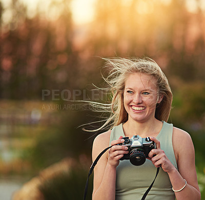 Buy stock photo Cropped shot of a young woman taking photos on her camera outside