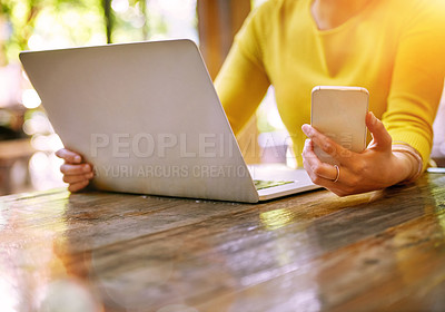 Buy stock photo Cropped shot of an unrecognizable young woman using her laptop outside
