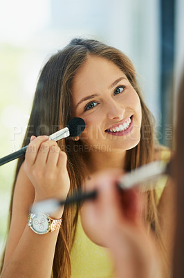 Buy stock photo Portrait of an attractive young woman applying makeup to her face with a brush