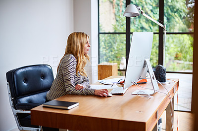 Buy stock photo Shot of a young woman working on a computer while sitting at a desk in her home office