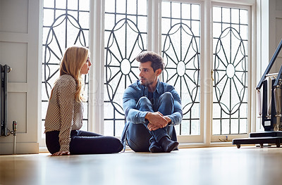 Buy stock photo Shot of a young couple talking together while sitting on their living room floor
