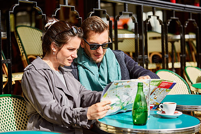 Buy stock photo Shot of a smiling couple sitting together at a table at a sidewalk cafe in Paris reading a map