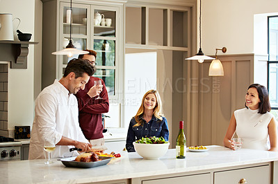 Buy stock photo Shot of a group of friends talking and drinking wine while preparing a meal together