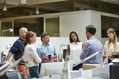 Buy stock photo Shot of a group of business colleagues talking together while standing in a large office