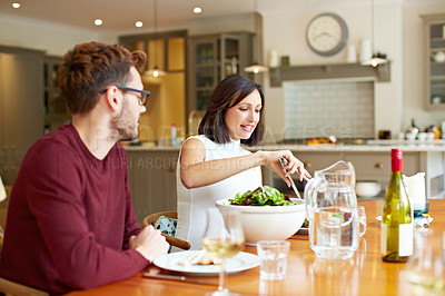 Buy stock photo Shot of a young couple enjoying a home-cooked dinner together