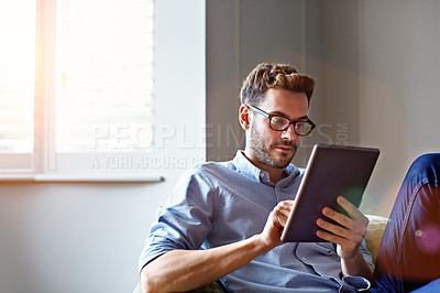 Buy stock photo Shot of a young man sitting on his sofa at home using a digital tablet